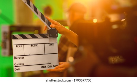 Close up Shot On Film Studio Set Young Camera Assistant Holds Empty Clapperboard. In the Background Director Shooting Green Screen Scene. History Costume Drama Movie.