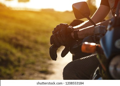 Close shot on man's hands in dark leather gloves. Side mirror of a motorbike and a relaxed hands of biker.