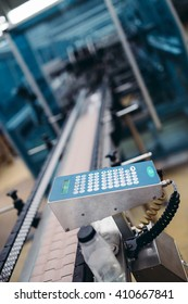 Close up shot on remote controller of robotic line for bottling pure spring water. Selective focus.