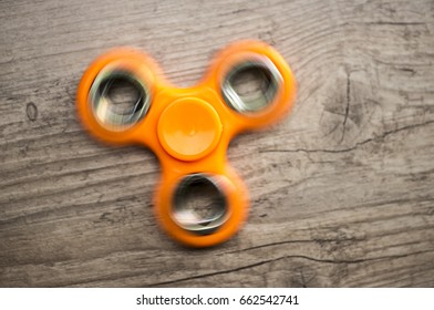 Close up shot of an orange fidget spinner while spinning
