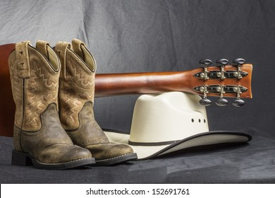 A close shot of a pair of boots. cowboy hat and a guitar handle.