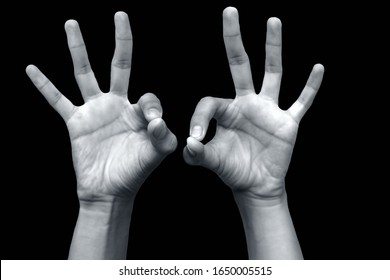 Close up shot of pair of extended male hands doing demonstrating chin mudra or mudra of consciousness isolated on black background. Horizontal shot of chin mudra demonstration.