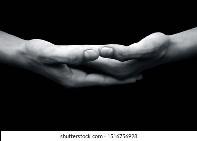 Close up shot of pair of human hands with open hands stacked hands-on each other isolated on a black background and doing famous  Dhyana Mudra or  Gesture Of Meditation.