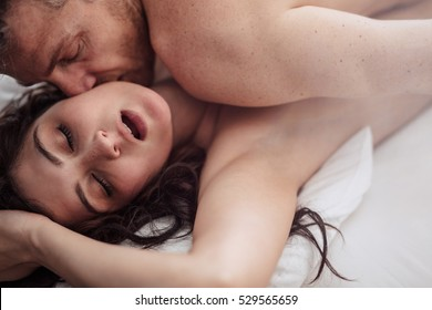 Close up shot of passionate young couple having sex on bed.