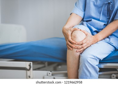Close up shot of patient sitting on bed in hospital suffering from knee pain