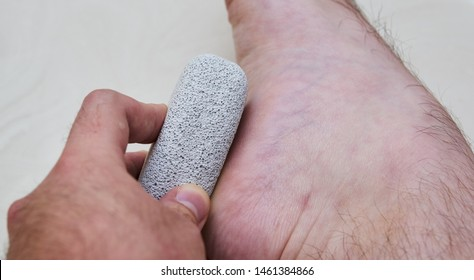 A close up shot of a pedicure stone (otherwise known as a pumice stone) being used on the heel of a foot.