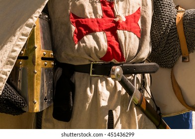 A close shot of persons torso dressed up historically to mimic a knights templar in full armour holding his helmet under the arm with his sword visible in the belt.