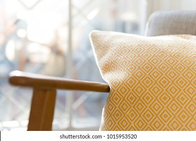 Close up shot of a pillow by the armrest of a vintage wooden chair