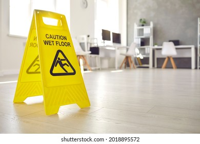 Close up shot of plastic standing sign that reads Caution Wet Floor and has figure of man who slips and falls office interior in blurred background. Commercial janitorial and cleaning service concept