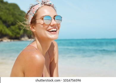 Close up shot of pleasant looking female wears headband and sunglasses, travels in tropical country, poses against warm peaceful ocean, blue sky and rocky cliff in background. Good relaxation