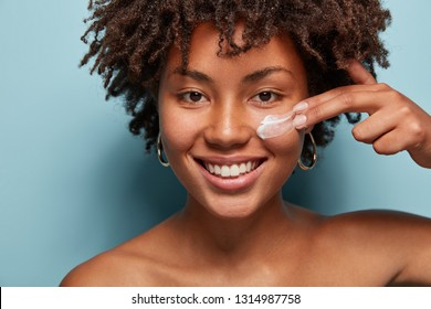 Close up shot of positive dark skinned woman with curly hair, appiles face cream on cheek, poses nude against blue background, cares of beauty, uses cosmetic product. Natural beauty concept.