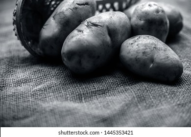Close up shot of potato or aloo or alu on jute bag surface along with two vegetable and fruit hampers.