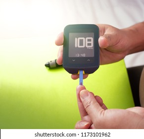 Close up shot of pregnant woman's hands making blood sugar level test by Glucose meter using as indicator of diabetes, and for pregnancy awareness of glycemia, health care concept.