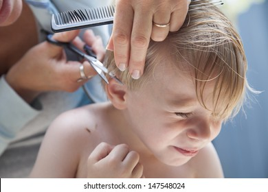 Close up shot of preschool aged boy enduring getting his hair cut in a backyard setting with a painful expression on his face.