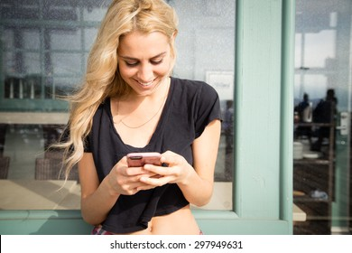 Close up shot of a pretty young woman texts on her mobile phone. She is smiling and happy, She looks like a California Beach girl. She is outside on a summer day on a boardwalk.