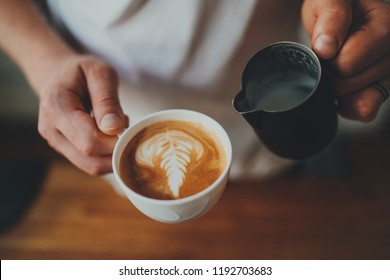 Close up shot of professional barista holding cup of fresh cappuccino with beautiful rosetta flower while working at the bar counter in cafe, coffee shop worker making cappuccino with latte art
