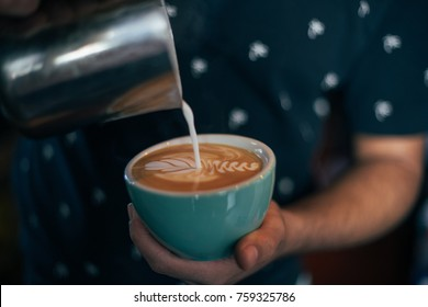 Close up shot of professional hipster barista at authentic artisan bar or cafe, preparing coffee with latte art on top, using fresh organic espresso shot from beans and hot steamed milk