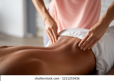 Close up shot of a professional masseuse doing massage with forearms and cubits for male client. Young man relaxing receiving facial massage at the spa center. Relaxation therapy resort recreation.