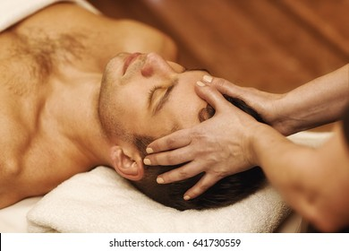 Close up shot of a professional masseuse doing face and head massage for her male client. Handsome young man relaxing receiving facial massage at the spa center relaxation therapy resort recreation