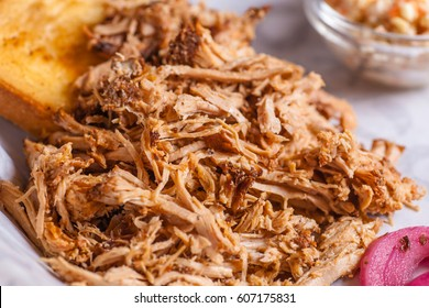 Close up shot of pulled pork fibers in a sandwich freshy served on a platter