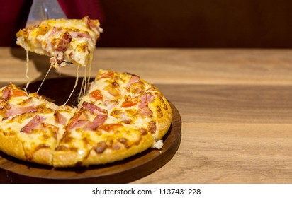 close up shot pulling hot pizza from wood plate and copy space in dark resturant background