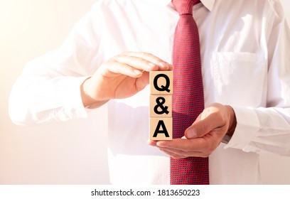 Close up Shot of Q and A wooden blocks in male hands of businessman, questions and answers