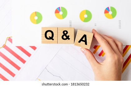 Close up Shot of Q and A wooden blocks on documents charts, female hand, questions and answers