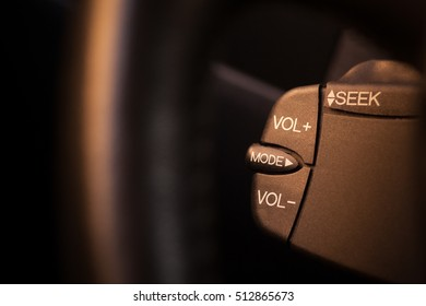 Close up shot with the quick control radio buttons near the steering wheel of a car.