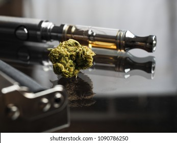 Close up shot of real cannabis or weed with cannabis oil in cartridge of vape  pen in the background, roller blurred in foreground and text space on the right under the dark theme
