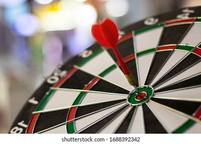 Close up shot red dart arrow on center of dartboard, metaphor to target success, winner concept, Isolated on white background with clipping path