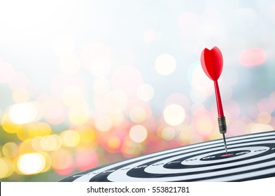 Close up shot red dart arrow on center of dartboard with transport and logistic concept blur truck and litghting background, metaphor to target success