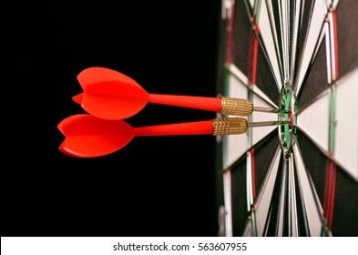 Close up shot red dart arrow on center of dartboard