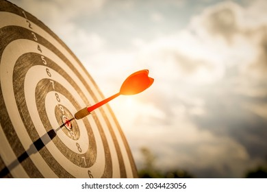 Close up shot red darts arrows in the target  of dartboard center on dark blue sky background. Business target or goal success and winner concept.