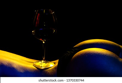 Close up shot of a red wine glass balanced on the center of a female's back next to her smooth butt that is lit up with red, blue and yellow studio lights, contrasting against the black background.