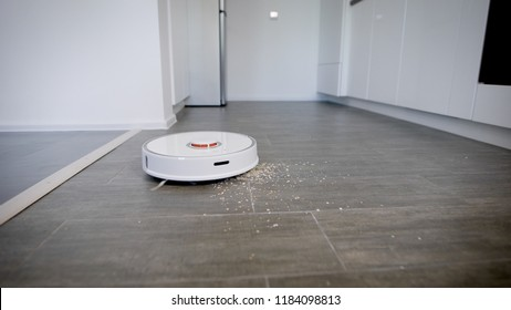 Close up shot of a robot vacuum cleaner cleaning kitchen parquet from crumbs and dust. Modern technologies, smart house.