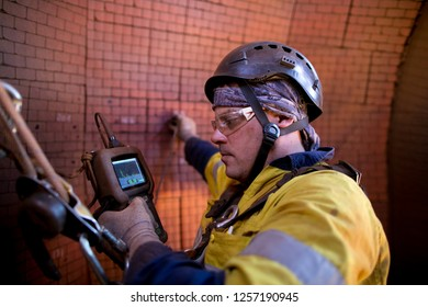 Close up shot of rope access Ultrasonic thickness technician inspector looking at scale on monitor instrument, while his right hand using detector gage commencing inspection on wall thickness