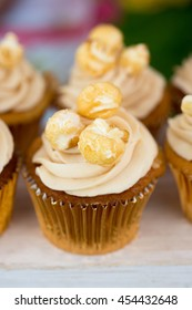 Close up shot of a row of butterscotch toffee cupcakes in gold paper cases with a toffee popcorn on the top.