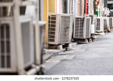 Close up shot of a row of old and inefficient air conditioning external units
