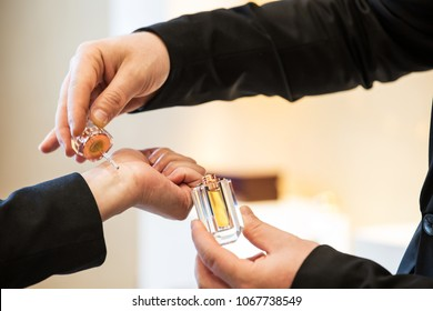 Close Up Shot Of A Sales Man's Hand Trying And Testing The Aromatic Oud Oil  On A Woman's Wrist And Holding The Jar Bottle On Other Hand