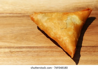 A close up shot of a samoosa isolated on a wooden board. This is a very popular snack in South Africa.
