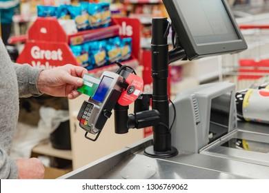 Close up shot of a senior man making a contactless payment at a supermarket till.