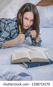 Close up shot of serious angry teenage girl doing her homework in the bed, prepares school test, writes in notebook with pen, clenches her fists.