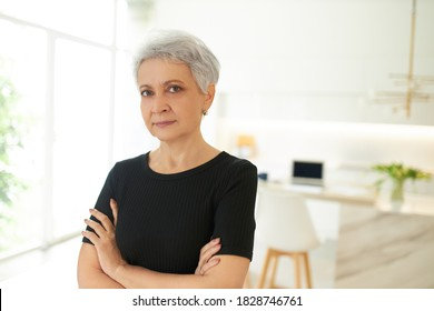 Close up shot of serious stubborn middle aged woman in black casual t-shirt posing at home in closed posture crossing arms on her chest and staring at camera with confident strict facial expression