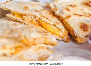Close up shot of several freshly served cheese quesadillas on a platter