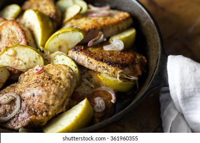 Close up shot of several pork chops, apples and onions in a cast iron skillet with it's handle wrapped in an old fashioned tea towel.