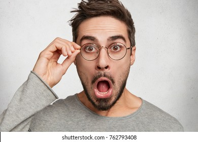 Close up shot of shocked stunned male stares at camera with jaw dropped out, touches spectacles, surprised to look at watch, realises that he missed train. Hipster guy reads shocking information