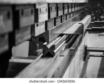 Close up shot from the side of big metal sheet bending machine. Bending blade is dropping down. Edited with black and white effect.