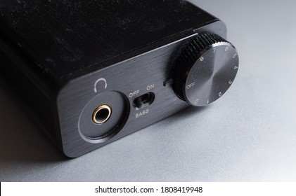 Close up shot of a small digital audio converter, or DAC, on a silver metallic surface.  Volume dial, headphone jack, and bass boost switch.  Black metal device for audiophiles.
