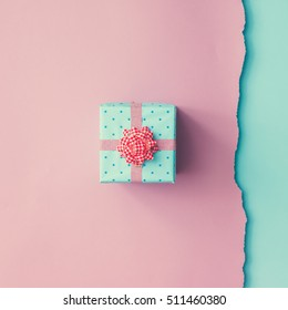 Close up shot of small gift wrapped with pink ribbon on pink blue background. Christmas background. Minimal concept. Flat lay. Top view.
