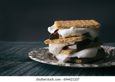 Close up shot of a s'more graham cracker sandwich with melting chocolate and gooey toasted marshmallows.